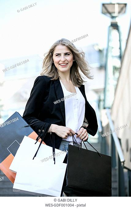 Portrait of smiling woman with several shopping bags