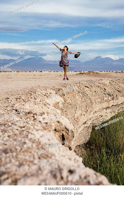 Chile, San Pedro de Atacama, woman in the desert with outstretched arms