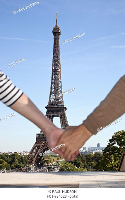 A man and woman holding hands in front of the Eiffel Tower, focus on background