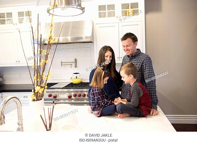 Couple and two children chatting in kitchen