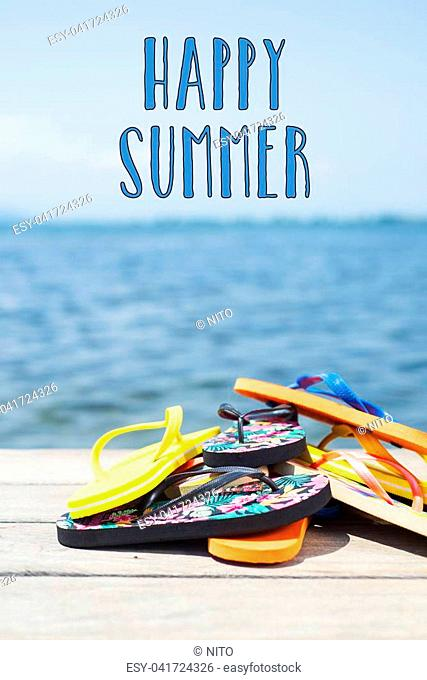 closeup of a pile of some different pairs of colorful flip-flops on a wooden pier next to the water, and the text happy summer