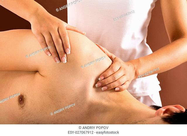 Relaxed Young Man Getting Massage In Spa