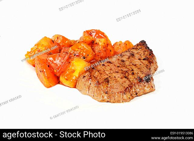 Plate with a beef steak and roasted tomatoes