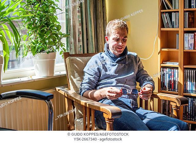 Tilburg, Netherlands. Living room portrait of an emotional young man