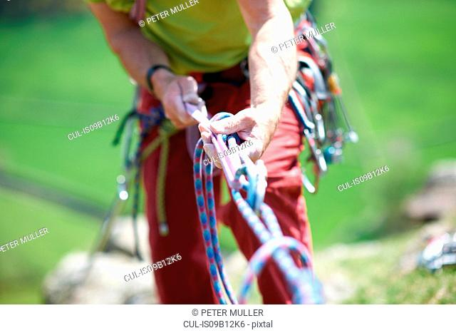 Cropped view of rock climber holding climbing rope