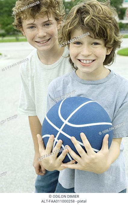 Two boys, one holding basketball, portrait