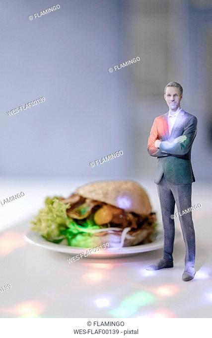 Miniature businessman figurine standing next to fast food surrounded by points of light