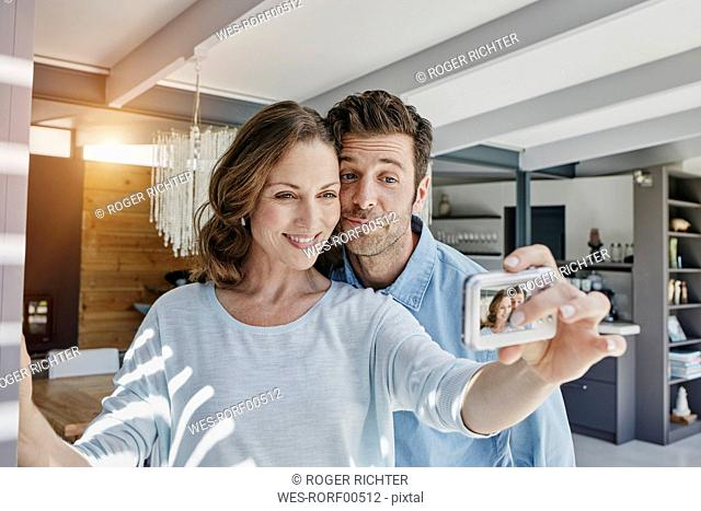 Happy couple taking pictures of themselves in their home