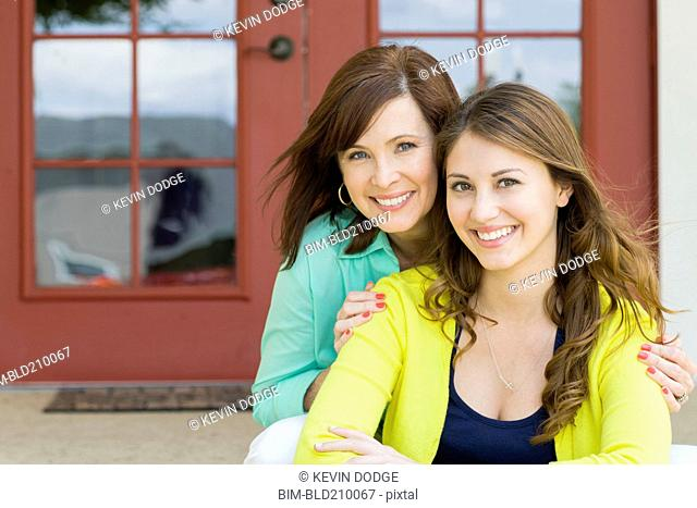 Caucasian mother and daughter smiling outdoors