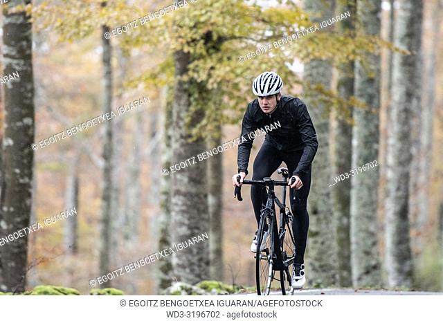 young cyclist boy riding alone at the forest in autumn. Aralar Natural Park, Navarra, Spain