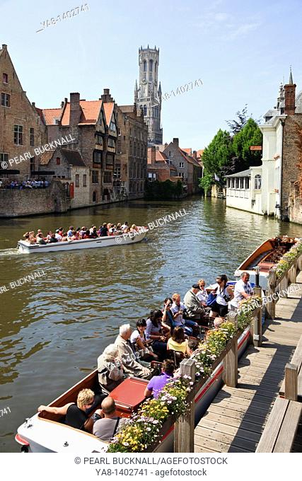 Rozenhoedkaai, Bruges, East Flanders, Belgium, Europe  Rosary quay with tourists onboard Dijver Canal cruise boats with Bell Tower beyond in the historic city
