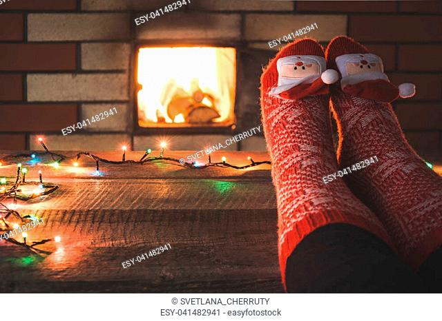 Feet in woollen red socks by the fireplace. Female relaxes by warm fire and warming up her feet in christmas socks. Close up on feet