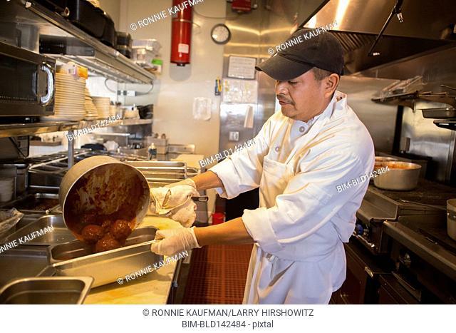 Hispanic chef cooking in restaurant kitchen