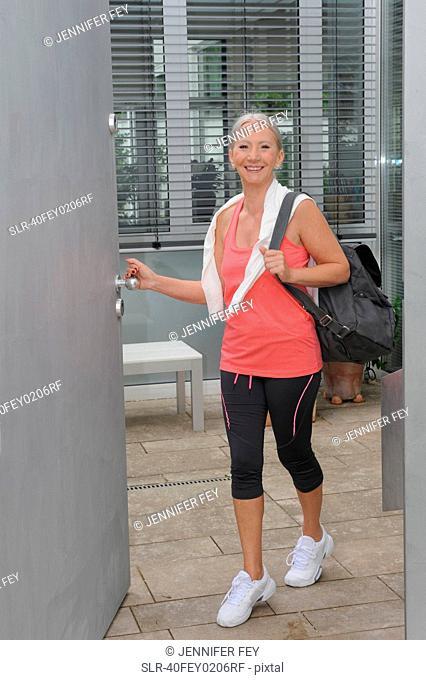 Smiling older woman carrying gym bag