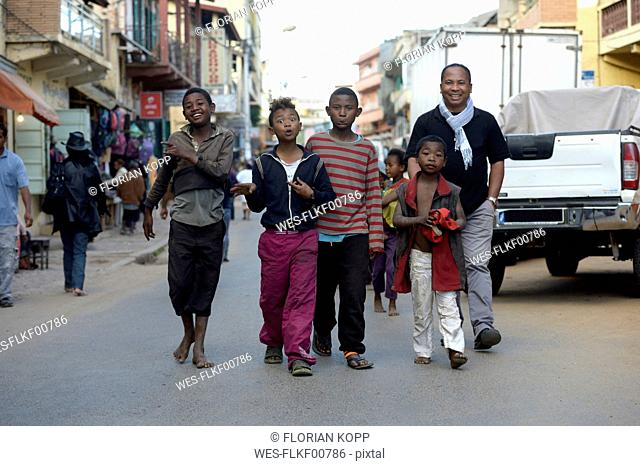 Madagascar, Fianarantsoa, Social worker walking in the street with a group of teenage street boys
