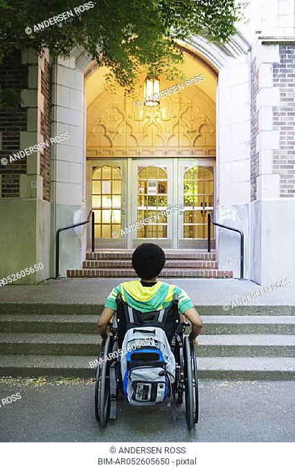 Man in wheelchair looking at steps