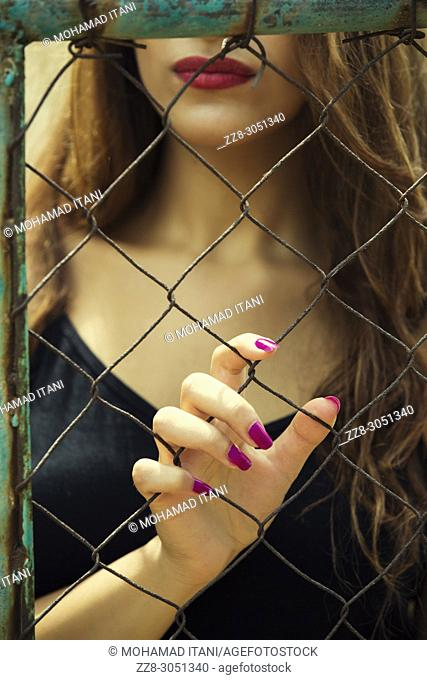 Close up of a young woman holding the fence