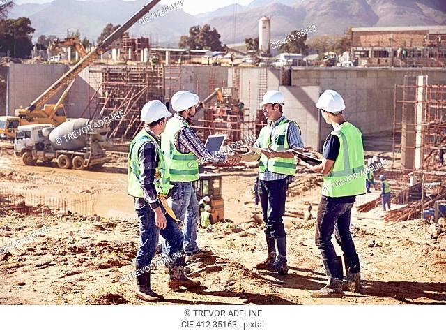 Construction workers and engineers shaking hands, meeting at sunny construction site