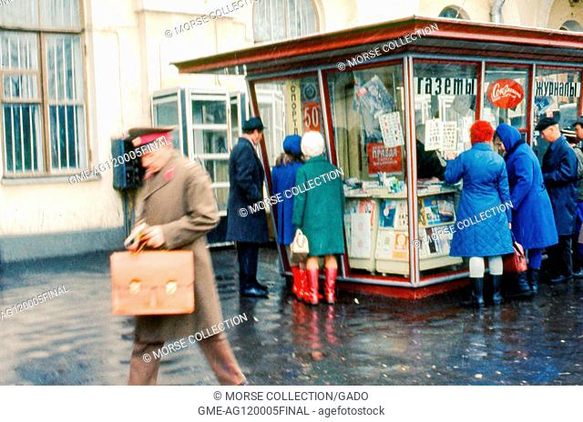 Scene on a Moscow street of people lining up outside of a newsstand kiosk, November, 1973. Signs in Russian advertise the sale of newspapers and magazines