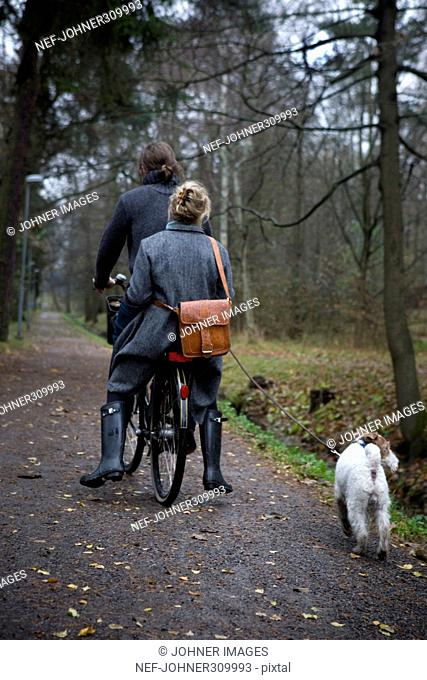 A couple on a bicycle excursion with their dog