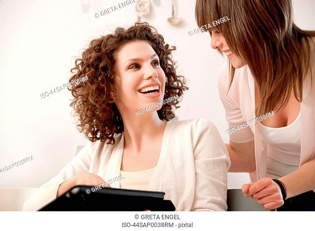 Smiling women talking indoors