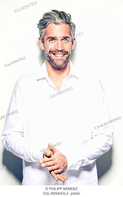 Portrait of mid adult man, hands together, smiling