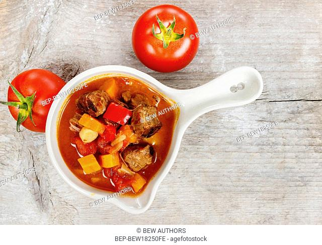 Top view of red soup with fresh vegetables and meat