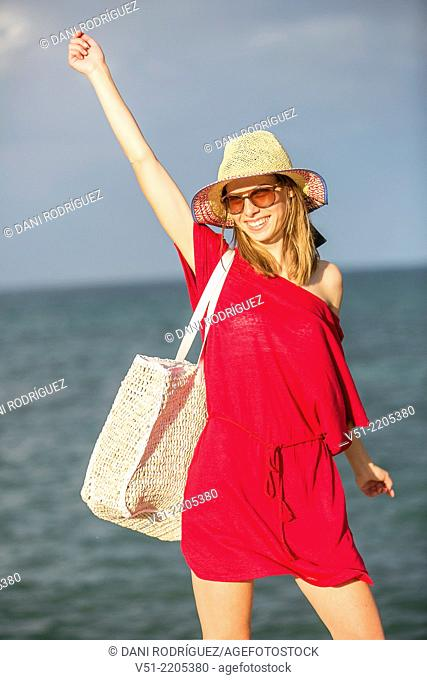 Young pretty woman arriving at the beach