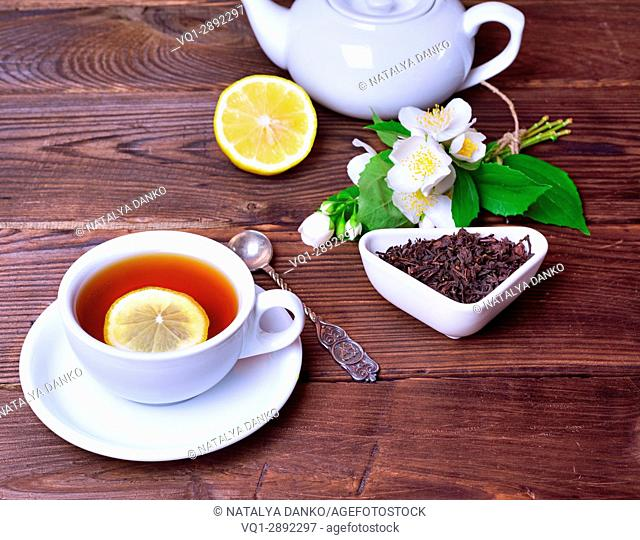 Black tea with lemon and brew on a brown wooden background, top view