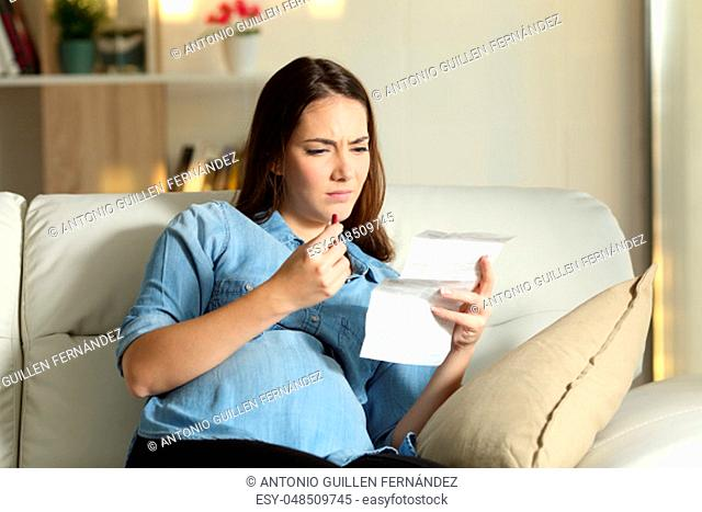 Confused pregnant woman reading a leaflet before take a pill sitting on a couch in the living room at home