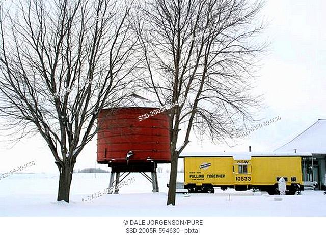 Train and old water tank in winter, Minnesota, USA