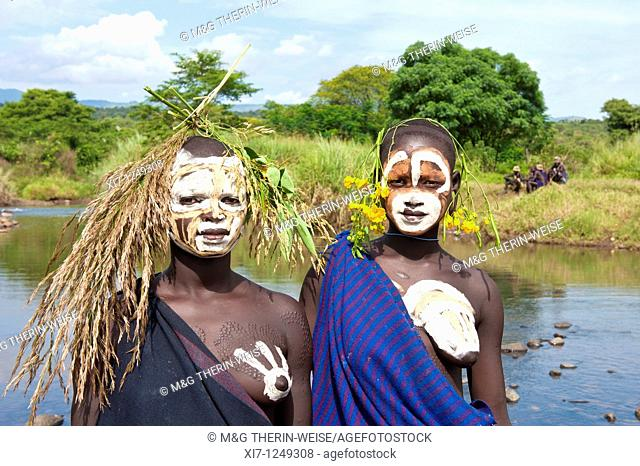 Young Surma women with body paintings in front of the river, Kibish, Omo River Valley,Ethiopia