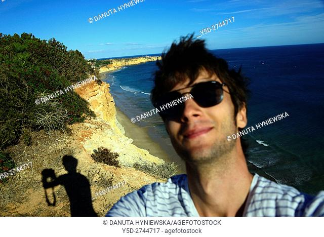 young man taking selfie with famous Porto de Mos beach in background, Lagos, Algarve, Portugal, Europe