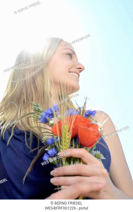 Smiling young woman with bunch of field flowers