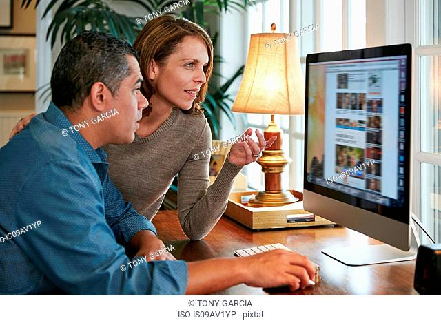 Side view of couple at desk using computer