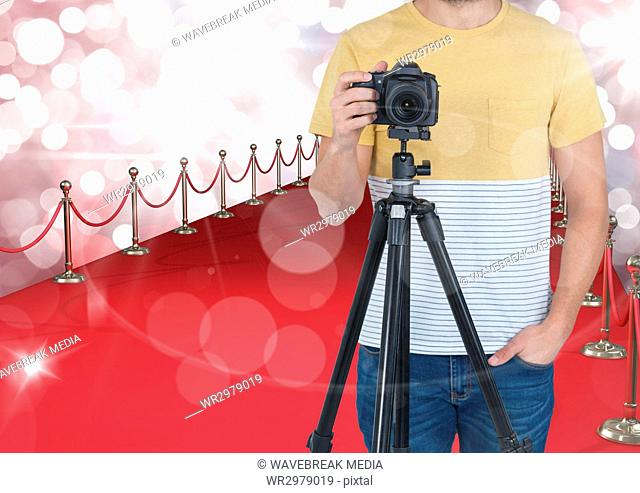 photographer with camera on tripod in the red carpet. Red and white bokeh background and flares ever