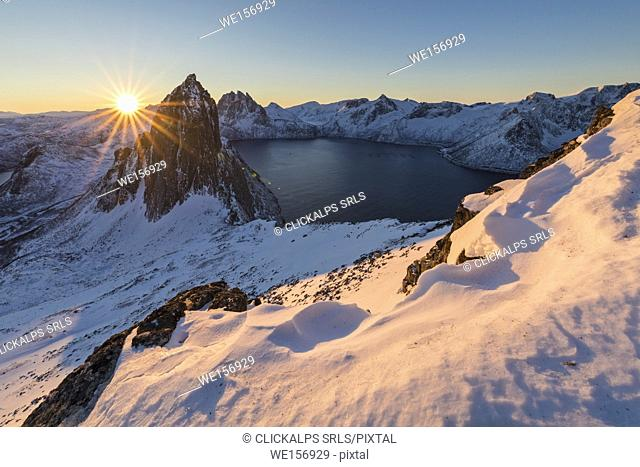 First lights of sunrise on Mount Segla and Mefjorden framed by the frozen sea seen from peak Hesten Senja Tromso Norway Europe