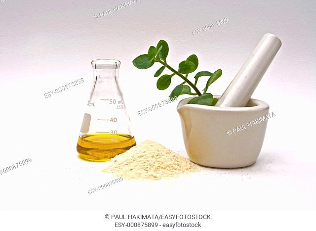 A yellow liquid in a flask with a powder in front and a white mortar with asome leaves in it on a white background
