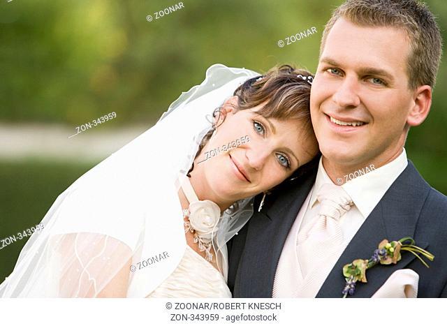 Braut legt ihren Kopf lächelnd auf die Schulter des Bräutigams