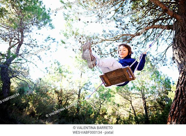 Spain, Siurana, little boy having fun on a swing in the forest
