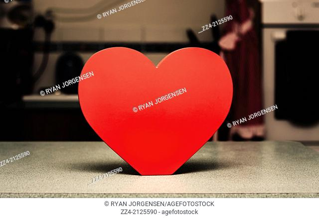 Healthy eating concept of a wooden heart shape chopping block sitting upright on kitchen bench. Cardiovascular copy space