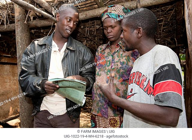 Aid worker talking to family baout milk yield records of cow. Rwanda. (Photo by: Wayne Hutchinson/Farm Images/UIG)