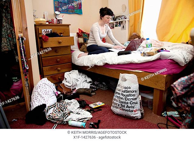 A young woman UK university student working on her laptop computer on the bed in an untidy bedroom