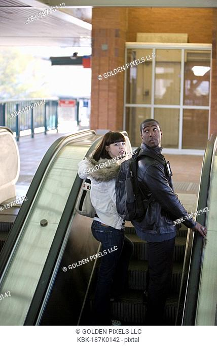 Young inter-racial couple standing on an escalator at a public train station
