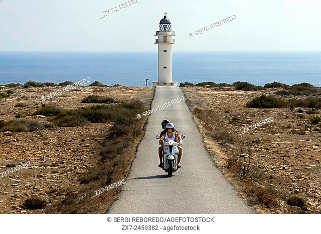 Two young motorcyclists on a long road to Es Cap de Barbaria lighthouse, in Formentera, Balears Islands. Spain. Barbaria cape formentera lighthouse road