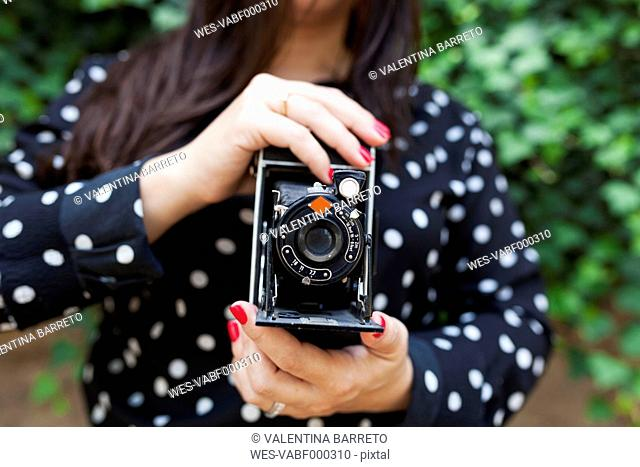 Hands of woman holding vintage camera