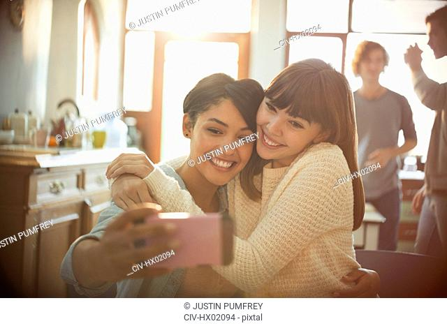 Young women friends taking selfie with camera phone in apartment