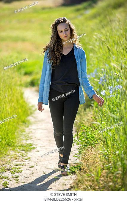 Caucasian woman walking on path near tall grass