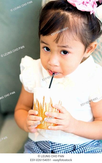 Adorable little girl drinking juice with paper cup