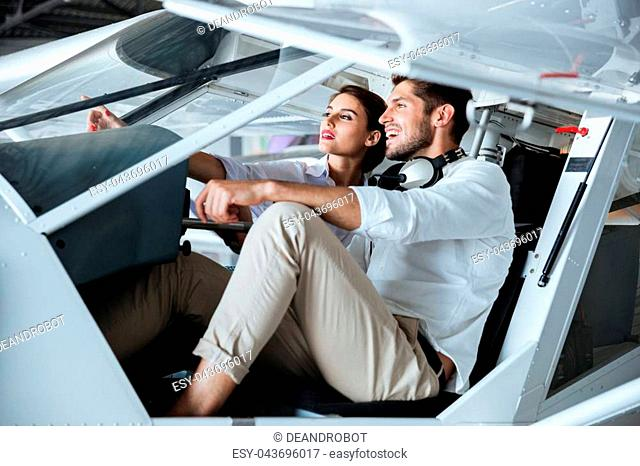 Beautiful young couple sitting and talking in cabine of small aircraft
